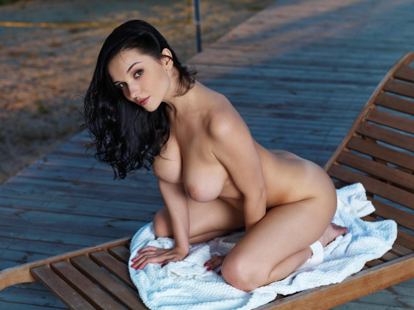 Приятная темноволосая девка Katie Fey лежит на шизлонге и демонстрирует голые сиськи