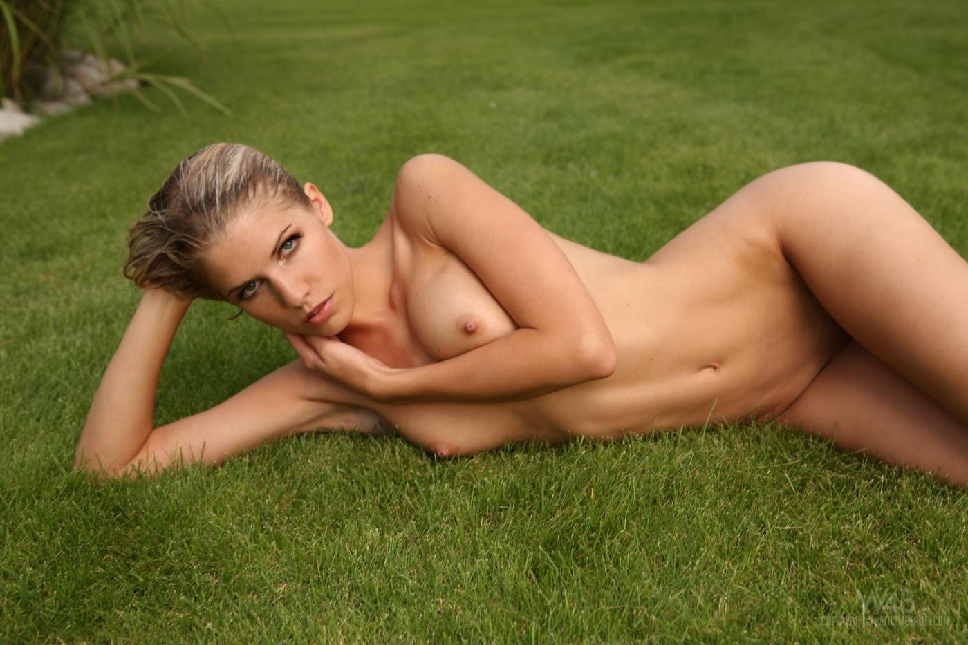 Полностью голая милашка Iveta Vale с обольстительной грудью красуется в траве и принимает уличный душ